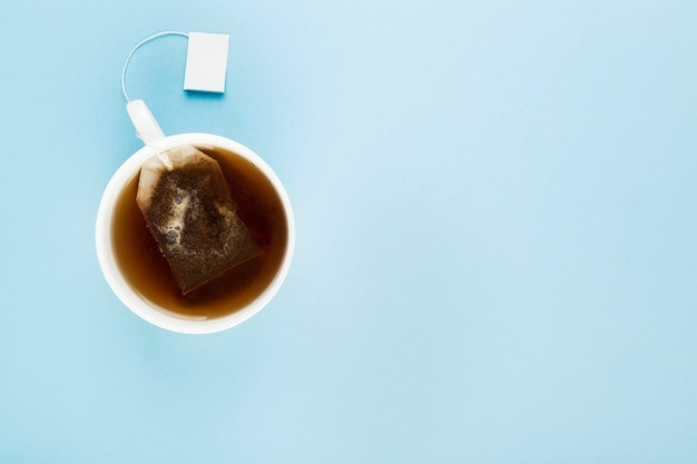 Cup of tea and tea bags on blue background. top view, copy space