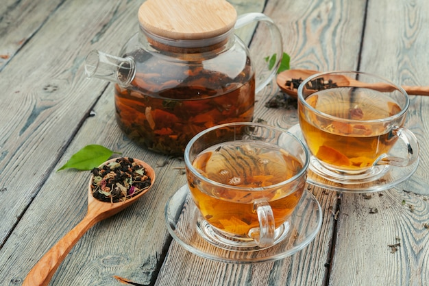 Cup of tea and tea leaves on wooden table