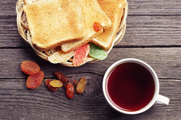 Cup of tea, toast bread and dried fruit on vintage wooden table. top view