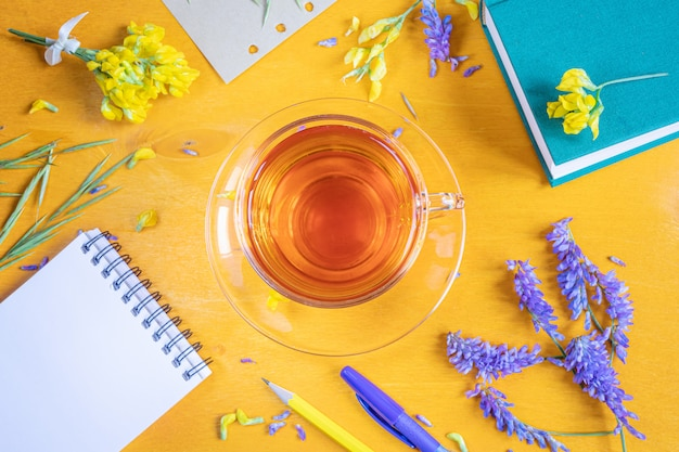Cup of tea in a transparent cup with a saucer, notebook, pen, pencil, wildflowers and herbs on a yellow wooden background.