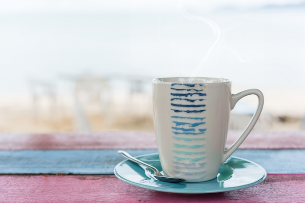 Cup of tea on vintage wooden table with blurred sea beach background