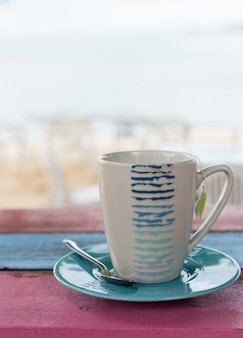 Cup of tea on vintage wooden table with blurred sea beach