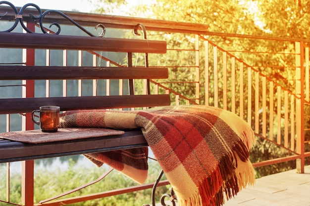Cup of tea and warm plaid on wooden bench outdoor