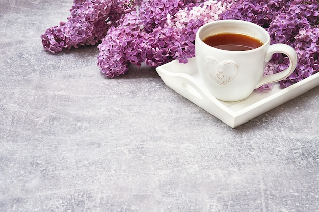 Cup of tea on white tray with lilac border on gray background. copyspace