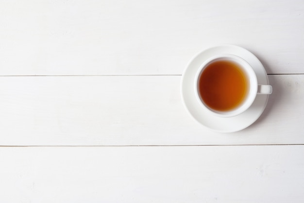 A cup of tea on white wooden background.
