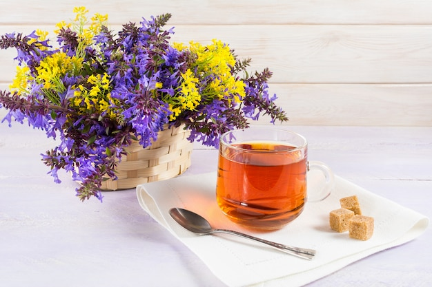 Cup of tea and wicker basket with purple and yellow flowers