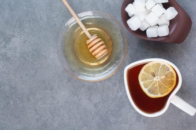 Una tazza di tè con zucchero e miele sul tavolo grigio.