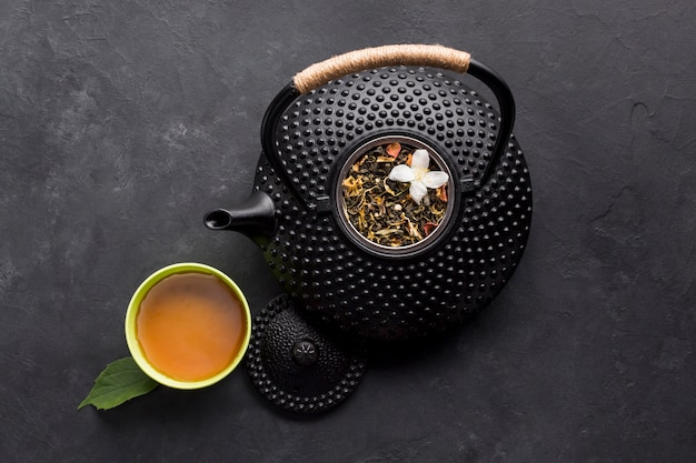 Cup of tea with aromatic dry herb and teapot on black surface