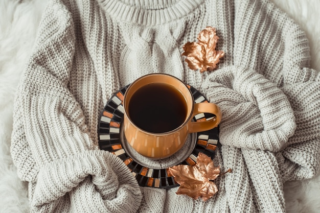 Cup of tea with autumn leaves and sweater