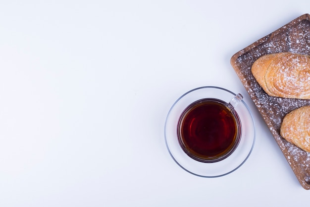 A cup of tea with badamburas in plate on white wooden background