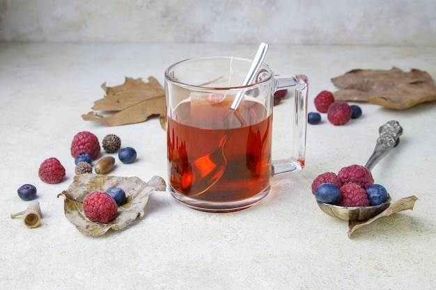 Cup of tea with berry and leaves