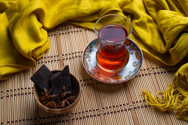 A cup of tea with black dark chocolate