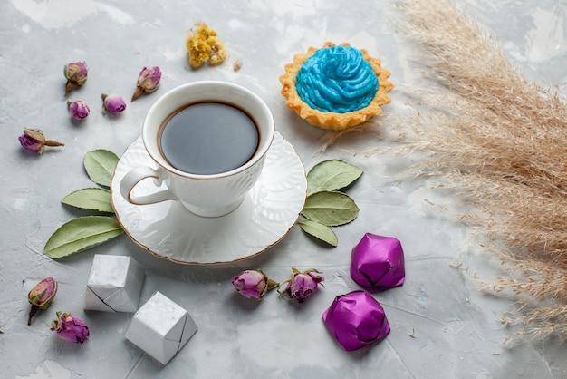 Tazza di tè con caramelle al cioccolato torta crema blu su caramelle di tè dolce bianco-grigio, biscotto