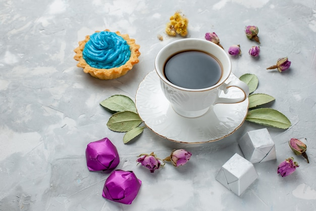 Cup of tea with blue cream cake chocolate candies on white-grey desk, biscuit sweet candy