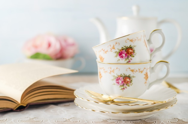Cup of tea with book, teapot and rose flowers on blue