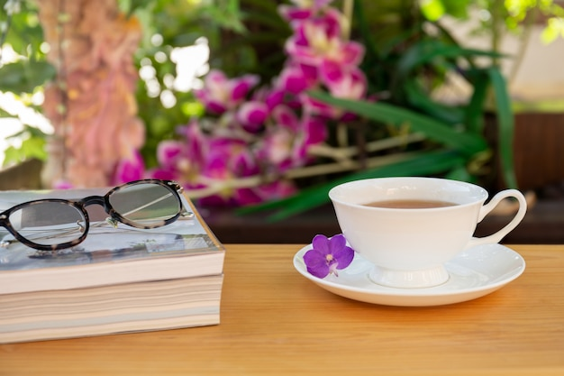 Cup of tea with books and eyes glasses on wooden table in garden.