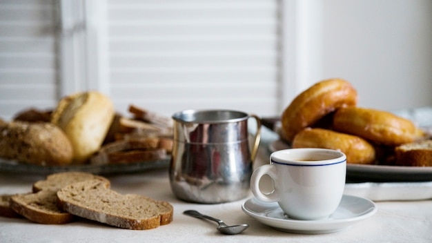 Cup of tea with bread and donuts on table