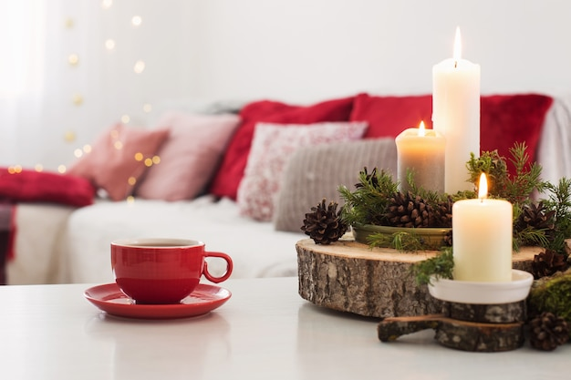 Cup of tea with burning candles on white table