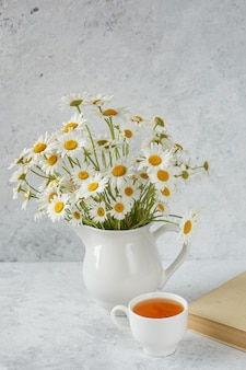 A cup of tea with chamomile and a bouquet of daisies in a vase