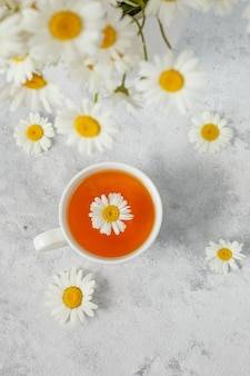 A cup of tea with chamomile and a bouquet of daisies