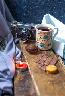 A cup of tea with chocolate bar and muffins on a piece of wood.