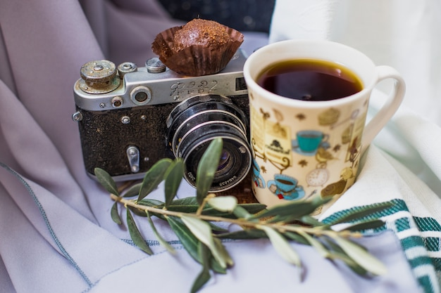 A cup of tea with a chocolate praline and a photo camera.