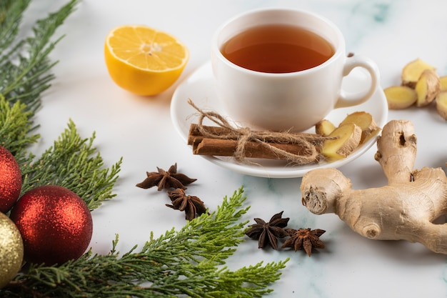 A cup of tea with cinnamon, lemon and ginger on a christmas decorated marble table.