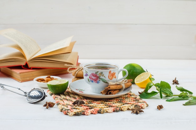 Cup of tea with cinnamon and lemon on square placemat with limes, a bowl of almonds,tea strainer and books on white surface