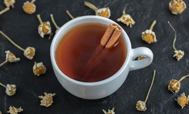 Tazza di tè con cannella e mucchio di camomille secche.