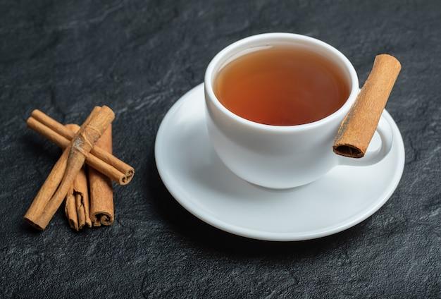 Una tazza di tè con bastoncini di cannella e infuso.