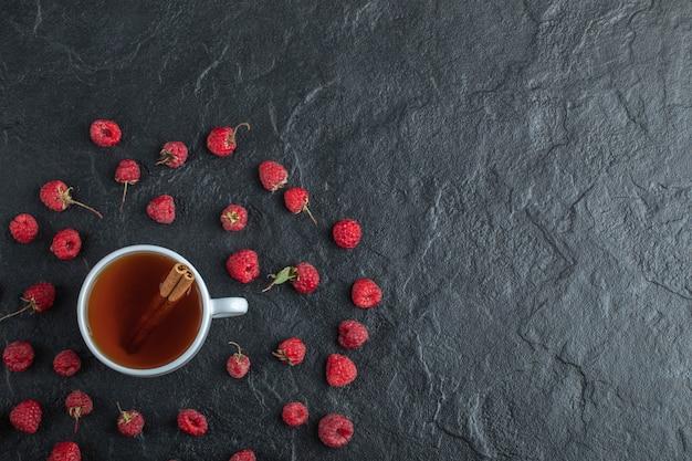 Tazza di tè con bastoncini di cannella e lamponi maturi.