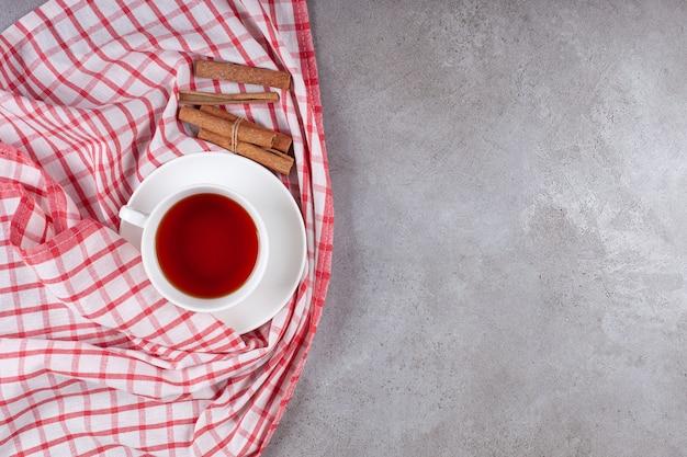 Una tazza di tè con bastoncini di cannella su una tovaglia
