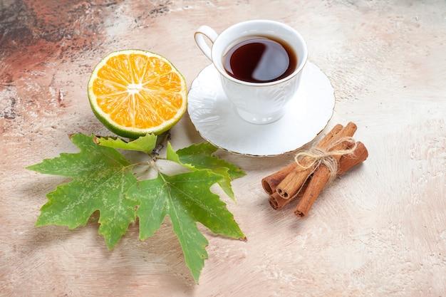Tazza di tè con limone cinnamonnd sulla luce
