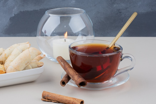 A cup of tea with cinnamons and cookies on white table.