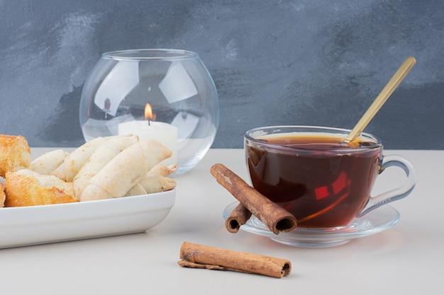 Una tazza di tè con cannellini e biscotti sul tavolo bianco.