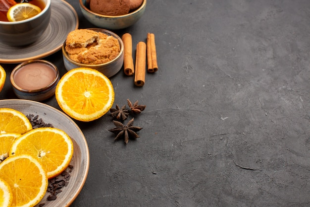 Cup of tea with cookies and fresh sliced oranges on dark