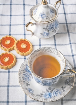 Cup of tea with cookies and sugar-bowl on squared cloth