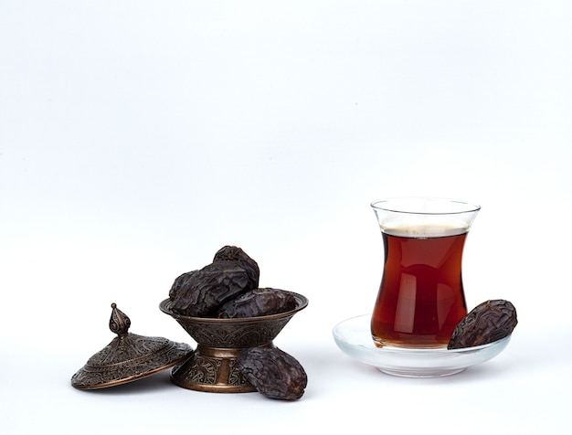 A cup of tea with dates on a plate isolated