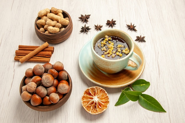 Cup of tea with different nuts on white