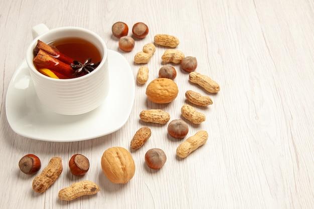 Tazza di tè con noci diverse su bianco