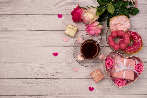 Cup of tea with donuts, fresh roses, more gifts, red ribbon on wooden table for valentines day