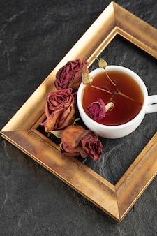 Una tazza di tè con rosa appassita e cornice su un tavolo nero.