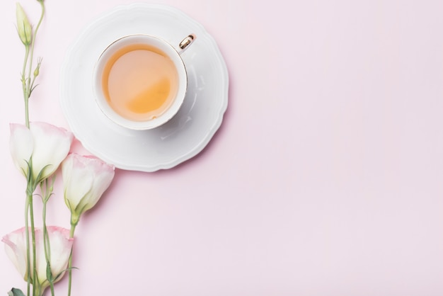 Cup of tea with eustoma flowers on pink background