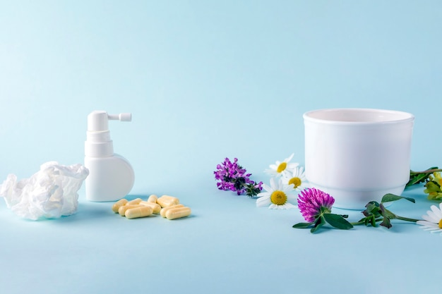 Cup of tea with flowers chamomile and blooming sally and pills, spray for runny nose and throat. seasonal diseases and treatment of colds, flu, heat. herbal medicine vs conventional medicine.