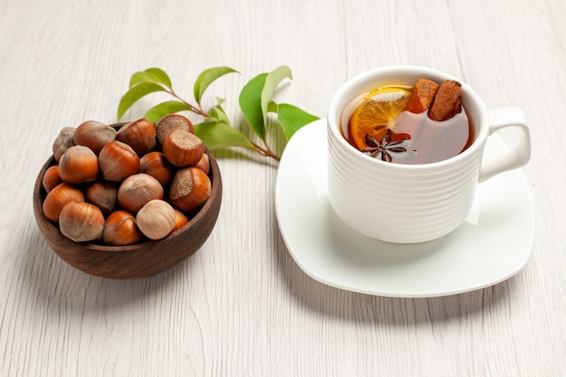 Cup of tea with fresh hazelnuts on white