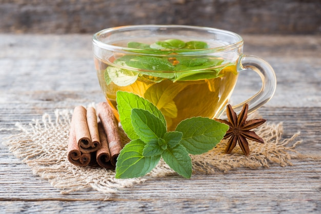 Cup of tea with fresh mint leaves and cinnamon anise