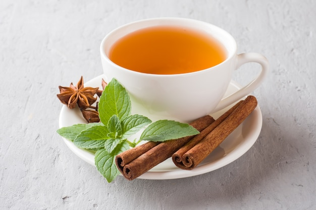 Cup of tea with fresh mint leaves and cinnamon star anise on a gray concrete