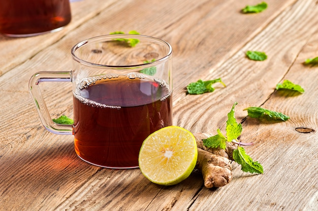 Cup of tea with ginger, lemon and mint on wooden table