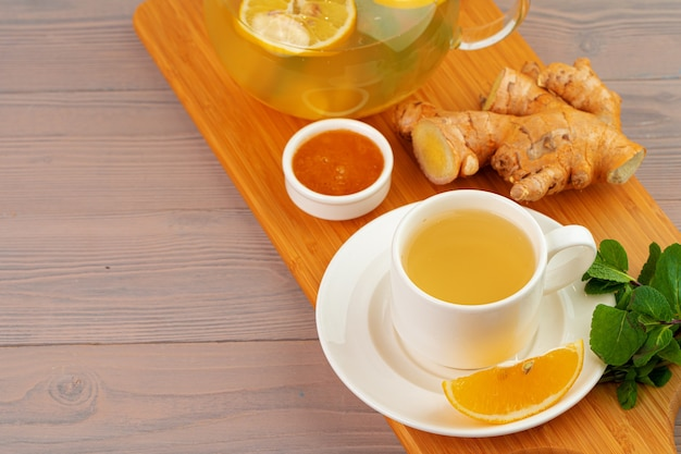 Cup of tea with ginger and mint on wooden table close up