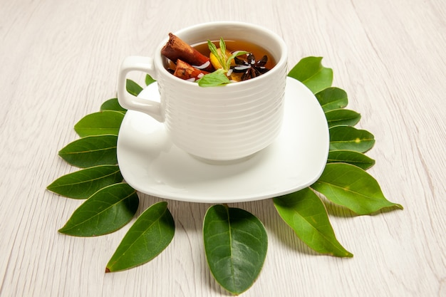 Cup of tea with green leaves on white